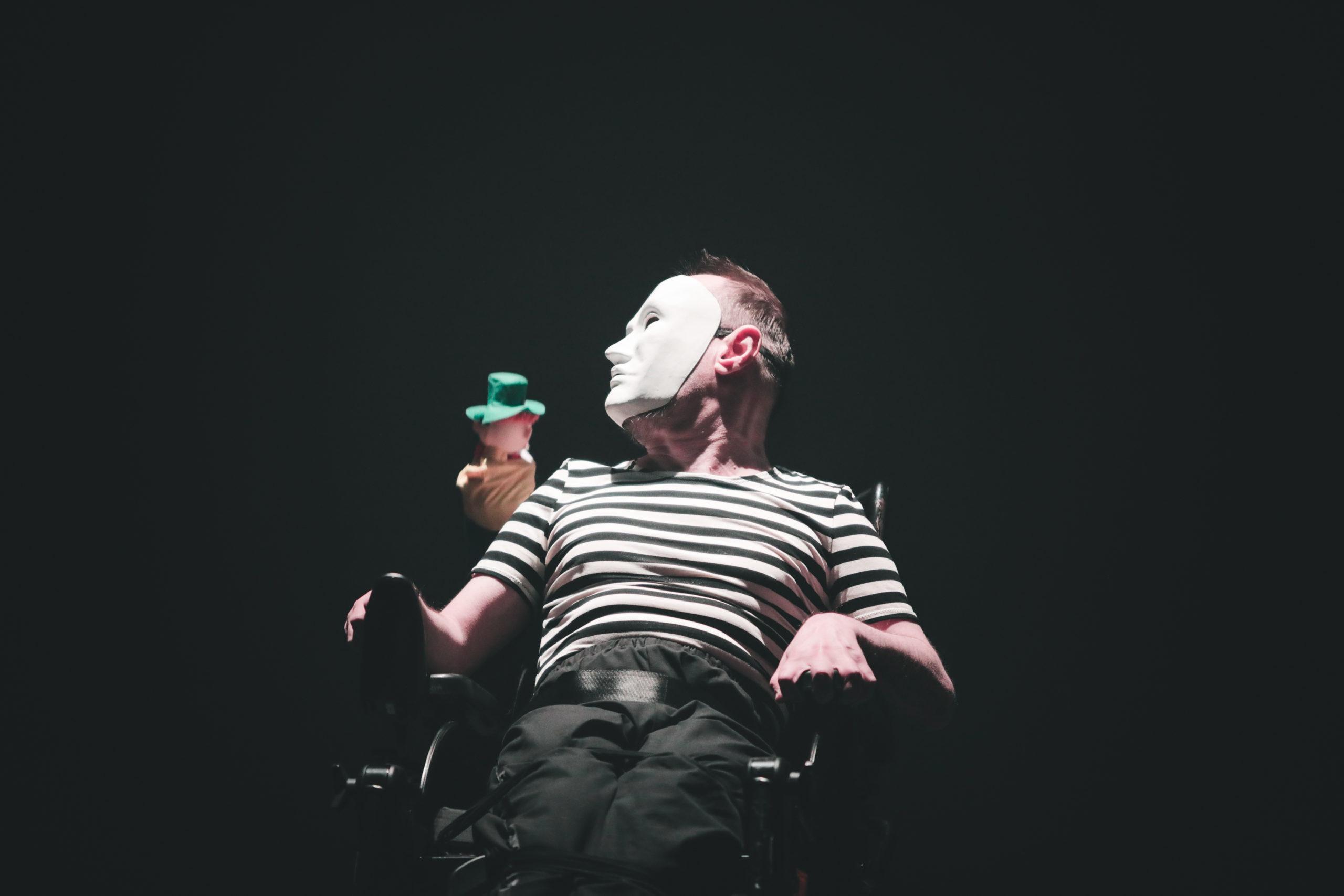 Danseur en fauteuil roulant masqué de blanc avec une marionnette